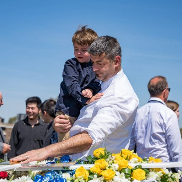 funeral photography - a son-in-law with his son farewelling the deceased at a Croatian funeral