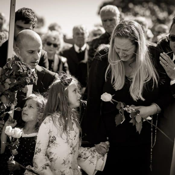 funeral photography - a daughter consoling her distraught mother st the graveside