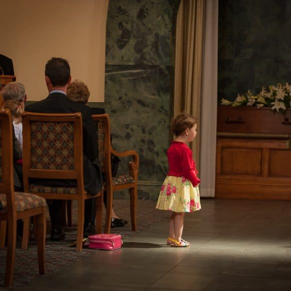 funeral photography - little girl contemplating during funeral service